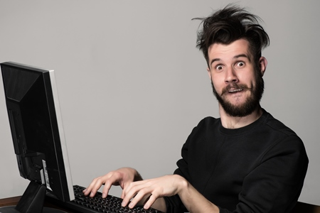 jeune homme avec barbe et style artiste semblant s'amuser en tapant sur un ordinateur