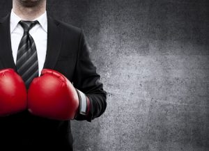 homme avec cravate muni de deux gants de boxes représentant le conflit